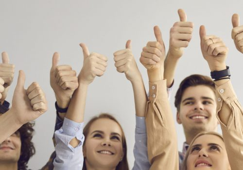 Group of happy satisfied young people raising hands in air and giving thumbs-up. Team of smiling men and women doing like gesture all together. Client satisfaction, positive attitude, teamwork concept